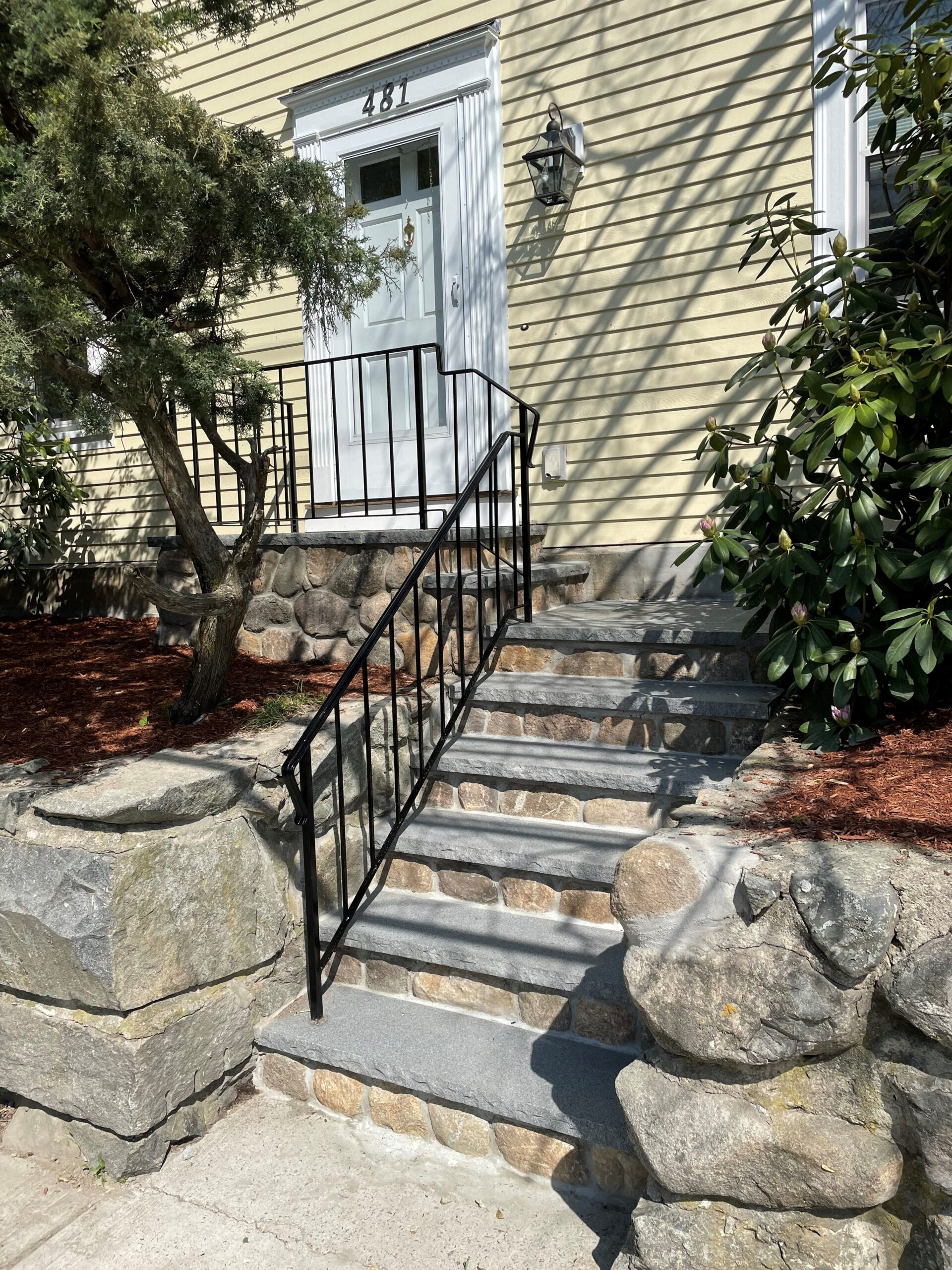 Stone And granite stairs with wrought iron railings